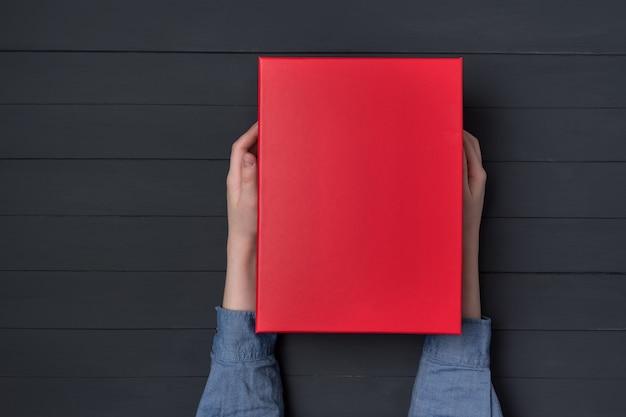 Las manos de los niños tienen una caja de regalo roja. fondo negro.