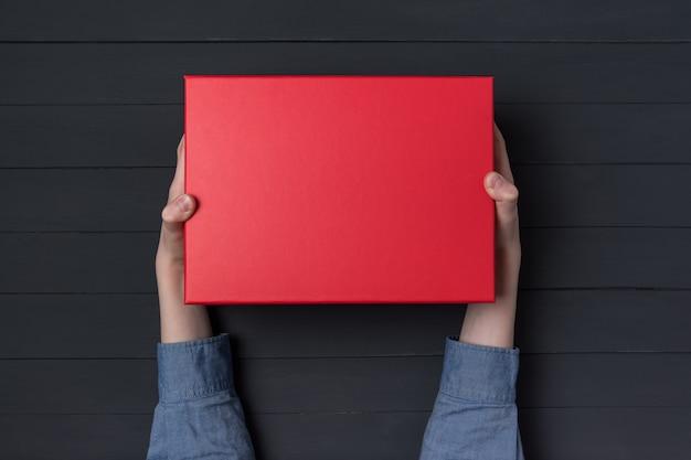 Las manos de los niños tienen una caja de regalo roja. pared negra vista superior.