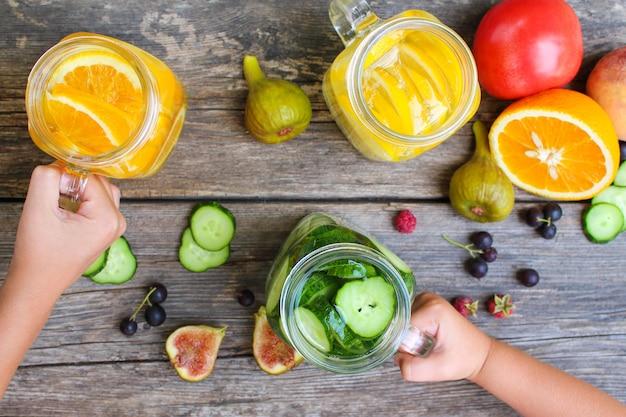 Las manos de los niños toman bebidas con fondo de frutas y verduras.