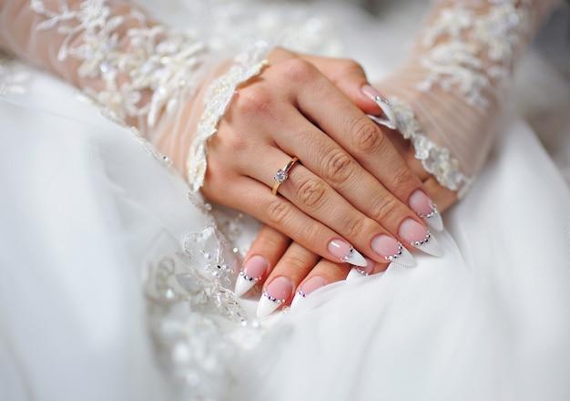 Las manos de una novia con un anillo y una boda manicura.