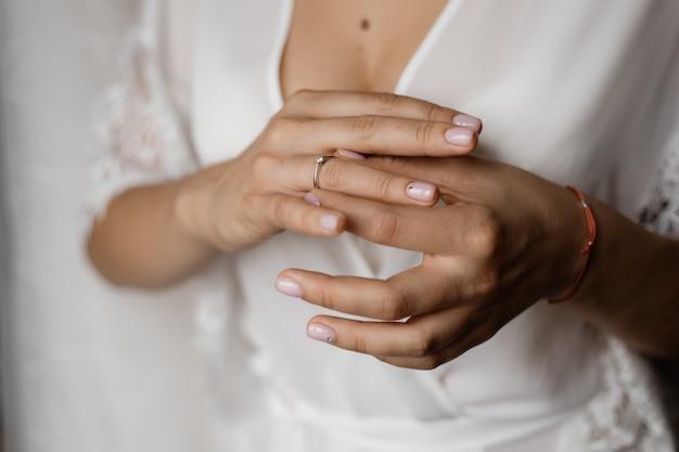 Manos de una novia con un anillo de compromiso con diamantes y una tierna manicura