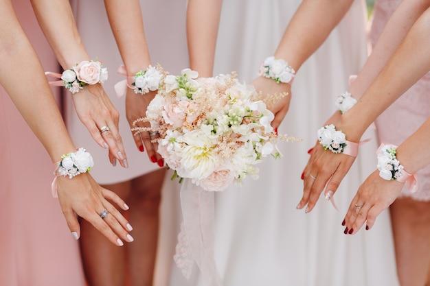 Manos de la novia y damas de honor con flores en tono rosa.
