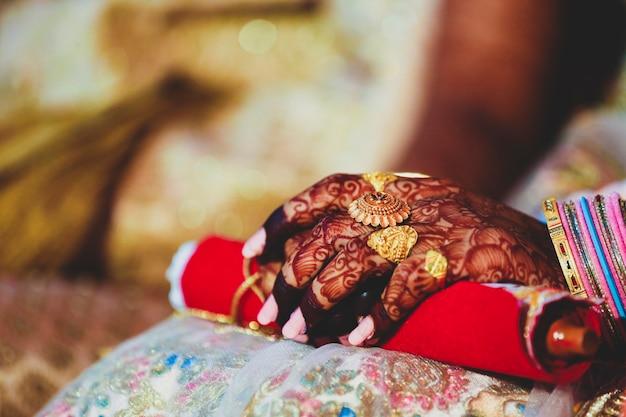 Las manos de la novia están bellamente decoradas con arte indio mehndi junto con joyas y brazaletes coloridos.