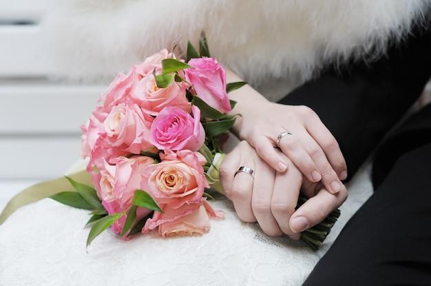 Manos de la novia y el novio con anillos de boda