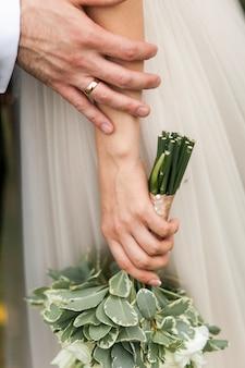Manos de la novia y el novio de primer plano. la novia está sosteniendo un ramo de boda.
