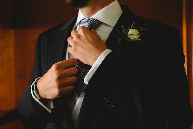 Manos de novio anudando su corbata a la moda nupcial antes de ir a la ceremonia.