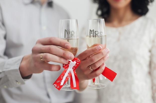 Manos de novio y novia con anillos sosteniendo copas con champán. boda, amor, romance, concepto de día de san valentín. lay flat, espacio de copia