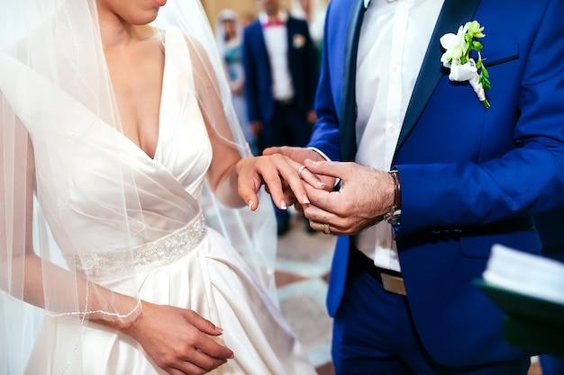 Las manos del novio y la novia llevan un anillo en el dedo el día.