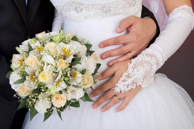 Manos de novios con anillos de boda y ramo de rosas