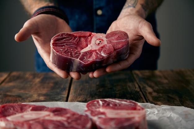 Las manos ofrecen un buen trozo de filete de carne con hueso.