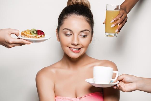 Manos ofreciendo pastel y bebidas a joven bella mujer