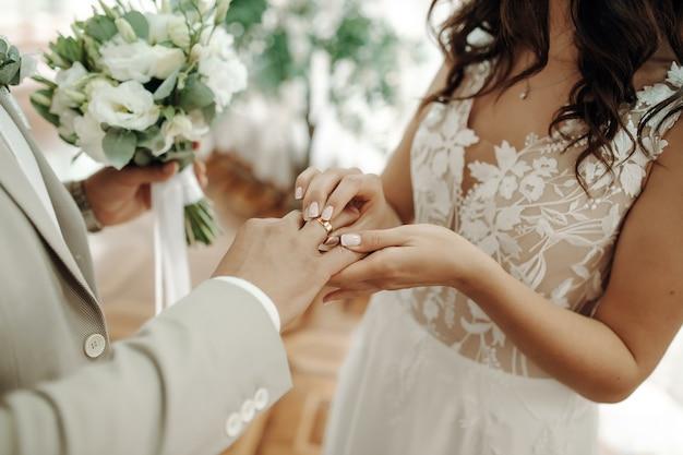 Manos omanos de recién casados con anillos de boda y un ramo de novia