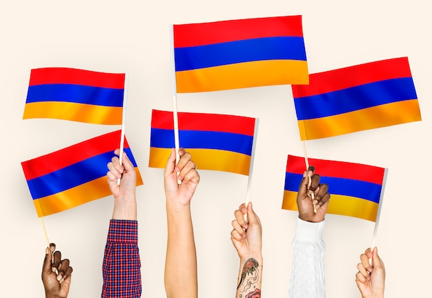 Manos ondeando banderas de armenia