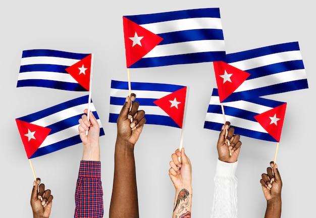 Manos ondeando banderas de cuba