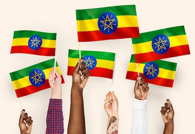 Manos ondeando banderas de etiopía
