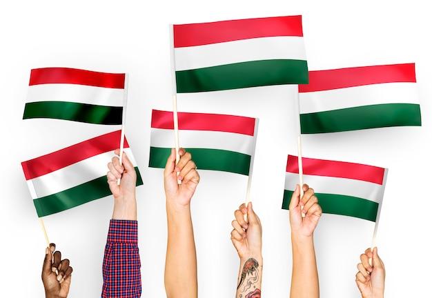 Manos ondeando banderas de hungría