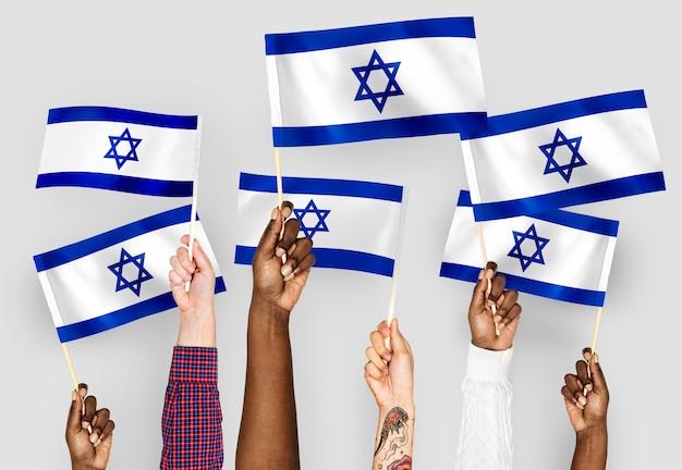 Manos ondeando banderas de israel