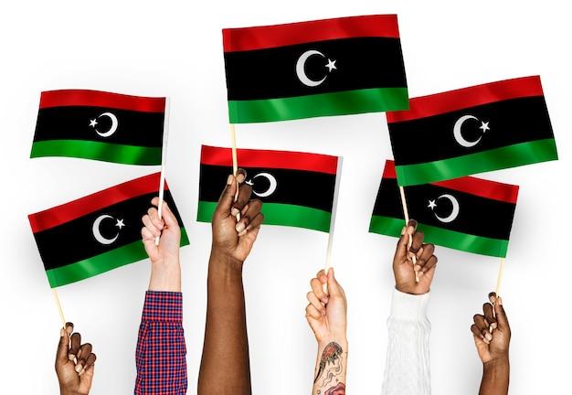 Manos ondeando banderas de libia