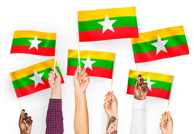 Manos ondeando banderas de myanmar