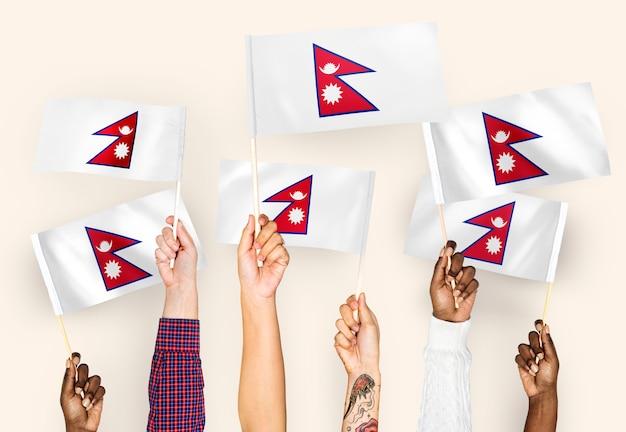 Manos ondeando banderas de nepal