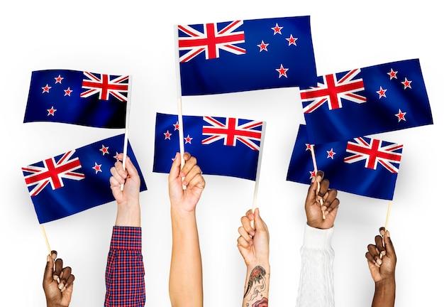 Manos ondeando banderas de nueva zelanda