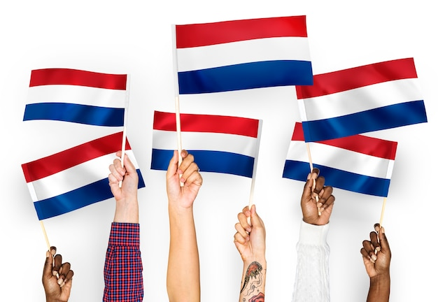 Manos ondeando banderas de los países bajos