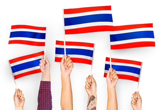 Manos ondeando banderas de tailandia