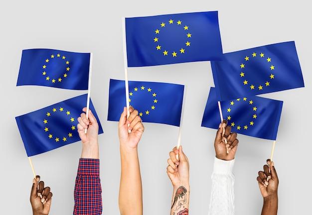 Manos ondeando banderas de la unión europea