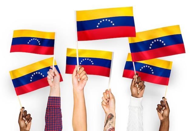 Manos ondeando banderas de venezuela