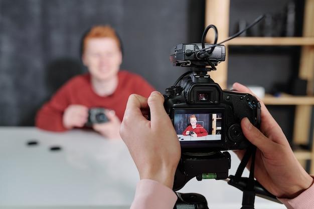 Manos del operador de video sosteniendo la cámara frente a un blogger masculino que muestra un nuevo equipo fotográfico mientras está sentado junto al escritorio