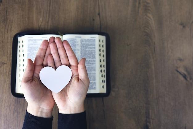 Manos a la oración femenina para cargar con el corazón roto en las manos sobre la biblia, concepto orar por la liberación, el pecado, no la libertad.
