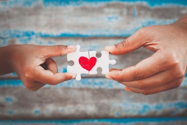 Manos de padres e hijos que conectan pieza de rompecabezas de pareja con corazón rojo dibujado