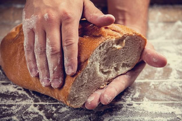 Manos de panadero con pan. foto con alto contraste.