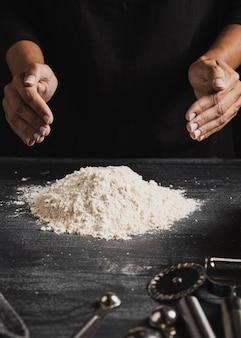 Manos de panadero de primer plano arreglando harina