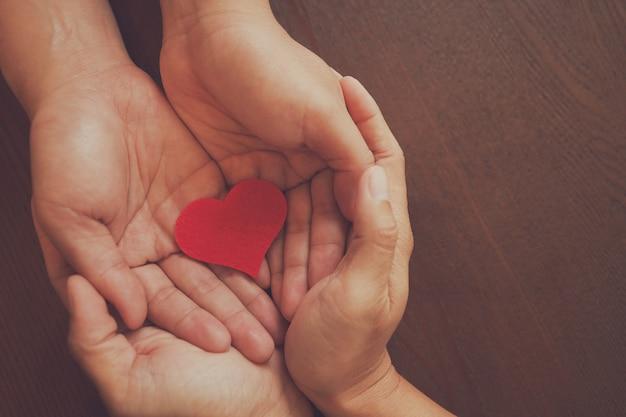 Manos de pareja hombre sosteniendo el símbolo del corazón rojo