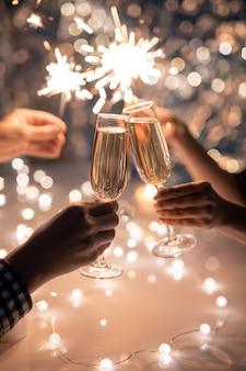 Manos de pareja joven tintineo con flautas de champán en el espacio de dos seres humanos sosteniendo brillantes luces de bengala