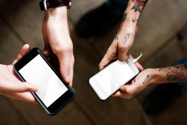 Manos de pareja utilizando teléfonos móviles.
