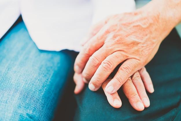 Manos de parejas asiáticas mayores se apoyan mutuamente, enfoque selectivo