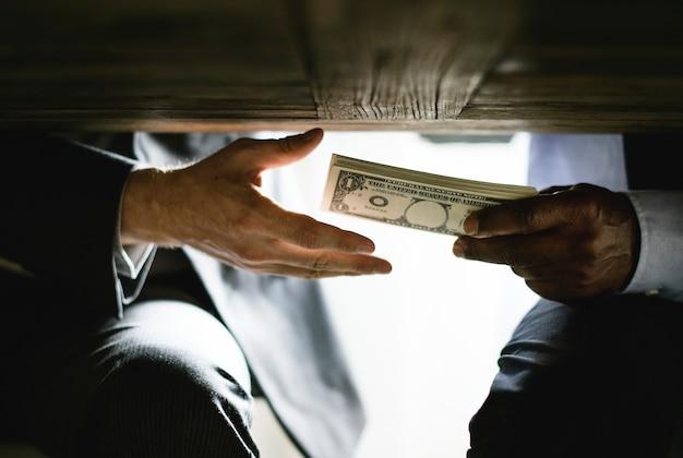 Manos pasando dinero bajo mesa soborno de corrupción