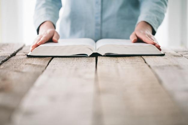 Manos pasando la página de una biblia