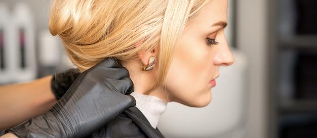 Manos de peluquería haciendo preparación antes de cortar el pelo a la joven mujer rubia en el salón de belleza