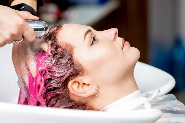 Manos de peluquería lavando el cabello