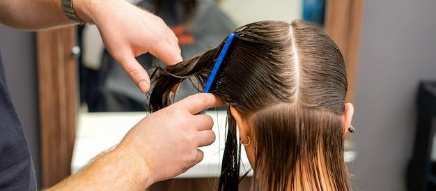 Manos de un peluquero peinando el cabello de una mujer joven dividida en secciones en la barbería