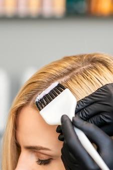 Manos del peluquero que tiñe el pelo de la mujer con el cepillo en el salón de belleza.