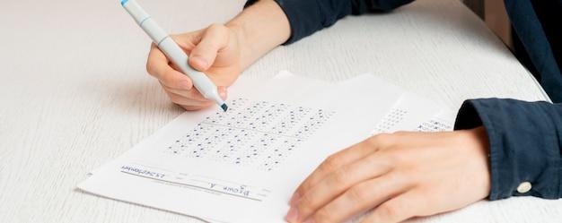 Las manos de la persona de cerca escribiendo respuestas en la prueba social en una hoja de papel