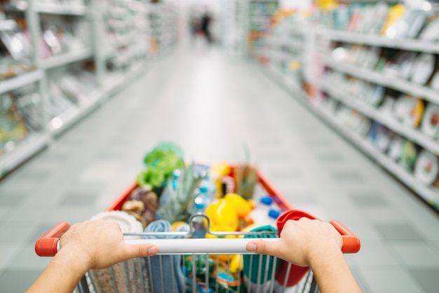 Las manos de la persona femenina arrastra el carro lleno de mercancías en un supermercado, de compras. cliente en la tienda, comprador en el mercado, concepto de compras