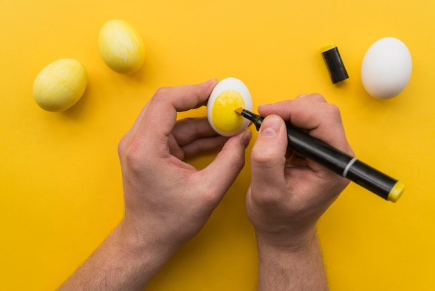 Manos de persona con marcador para colorear huevo.