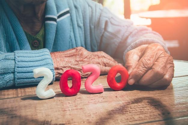 Las manos de la persona mayor que llevan a cabo el número 2020 en la tabla de madera. concepto: la población de más edad del mundo en 2020 crece dramáticamente.