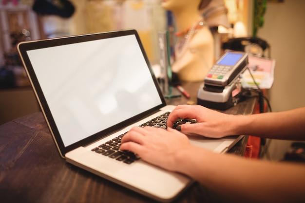 Manos del personal femenino usando la computadora portátil en un mostrador
