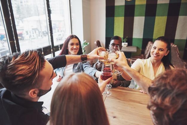 Manos de personas con copas de whisky o vino, celebrando y brindando en honor de la boda u otra celebración